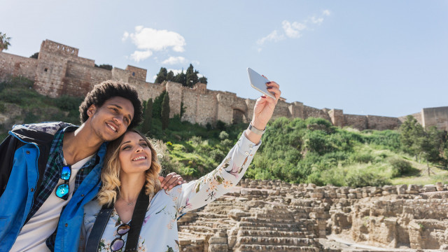 Interracial couple of friends travelers taking selfie